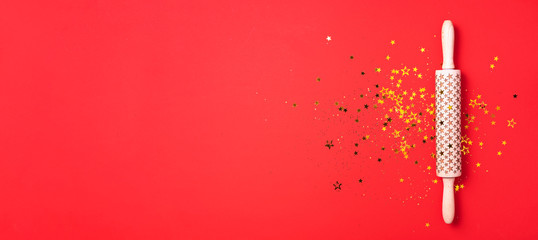 Rolling pin, gold glitter stars on red background. Top view. Copy space. Christmas baking concept. Holidays composition. Banner for menu, recipe, ingredients