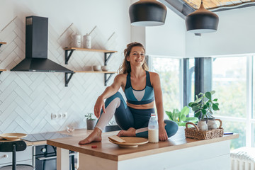 Portrait of a young athletic woman at home in the kitchen
