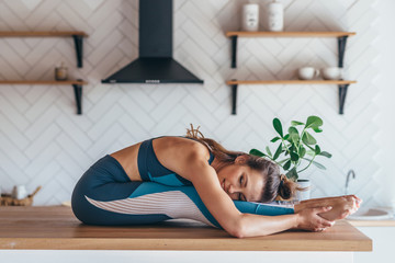 Woman stretching, doing seated forward bend on a table