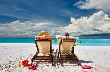 Couple in sun beds on a tropical beach