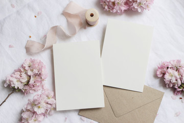 Wedding stationery mock-up scene. Blank greeting cards, envelope on linen tablecloth background...