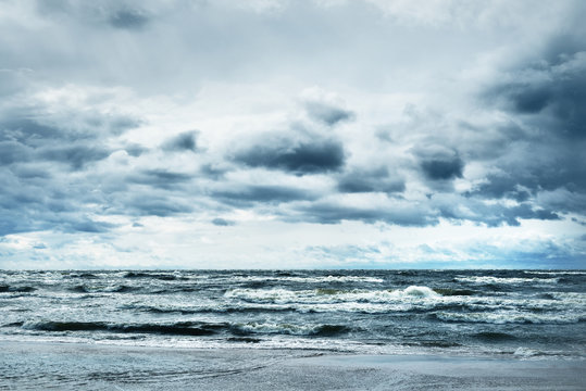 Dark blue cloudy sky above the Baltic sea, storm waves. A view from the seacoast. Latvia