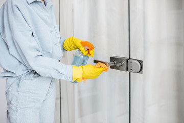 Woman in protective gloves disinfecting door handle while cleaning at home, close-up view on hands