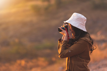 Happy smiling lifestyle portrait of pretty young woman traveler having fun while taking photos in evening on nature background. Beautiful girl photographer wear hat holding camera while travel at outd