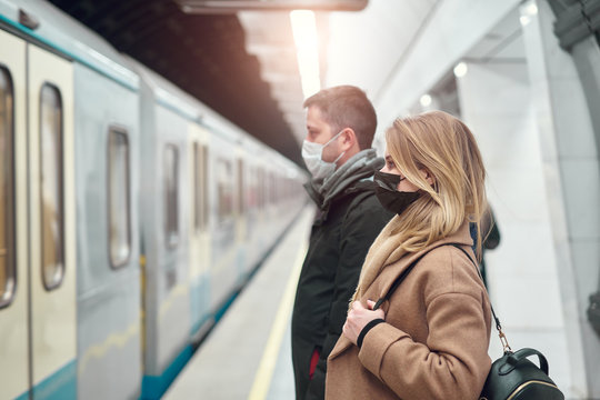 Side view of man and woman in medical masks standing near carriage in subway.