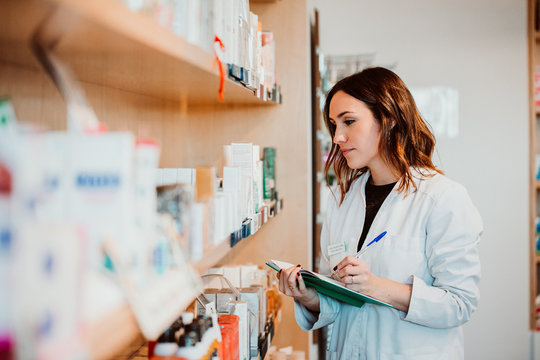 .Young female pharmacist working in her large pharmacy. Placing medications, taking inventory with her green notebook. Lifestyle