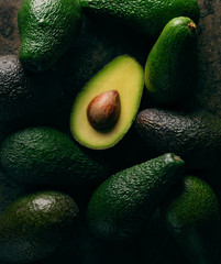 open avocado on group of avocados