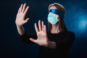 a girl blindfolded, with a blue ribbon, looking for coronavirus medicine