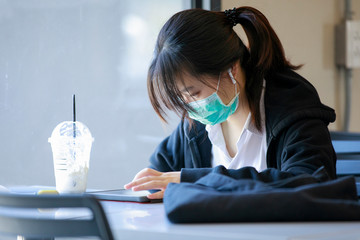 asian girl student in medical protective mask reading or studying from smart tablet