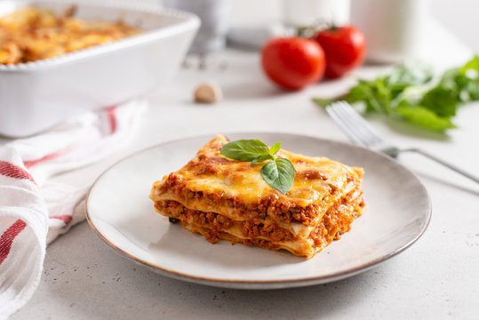 Piece of tasty hot lasagna served with a basil leaf on a gray plate. Italian cuisine, menu, recipe. Homemade meat lasagna. Close up