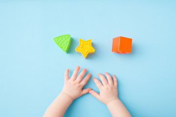 Baby hands playing with green triangle, yellow star and orange square shapes on light blue table background. Pastel color. Closeup. Toys of development for little kids. Top down view.