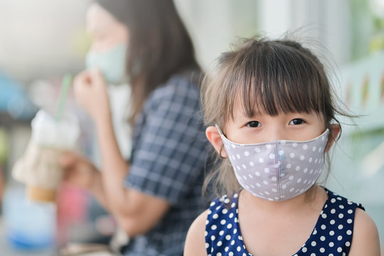 Little girl has fabric mask protect herself from Coronavirus,New Normal child leave the house with a mask on her nose for safety outdoor activity after COVID-19 outbreak,illness or Air pollution