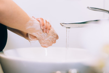 close up details of caucasian woman washing hands and cleaning hands from germs, bacteria and...