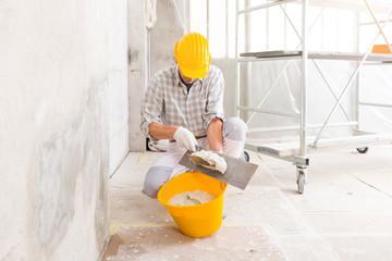 Plasterer loading new plaster from a bucket