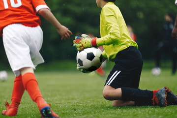 Junior Soccer Football Goalkeeper Catching Ball. Goalie in Action on the Pitch During Match. Goalkeeper on Knees in a Goal Play in a Game