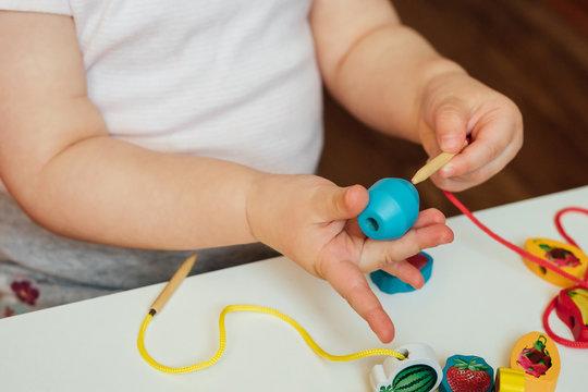 Child putting beads on a string. Bead stringing activity. Fine motor skills development. Lacing, threading.