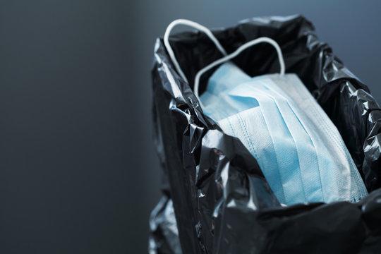 Used medical masks against coronavirus in trashcan. Corona virus or covid-19 concept.