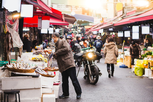 Market in Asia. Buyers with medical masks on their faces choose food in the market.