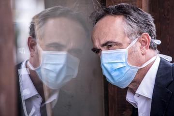 Ritratto di Uomo di mezza eta vestito in giacca con un mascherina azzurra si riflette nello specchio