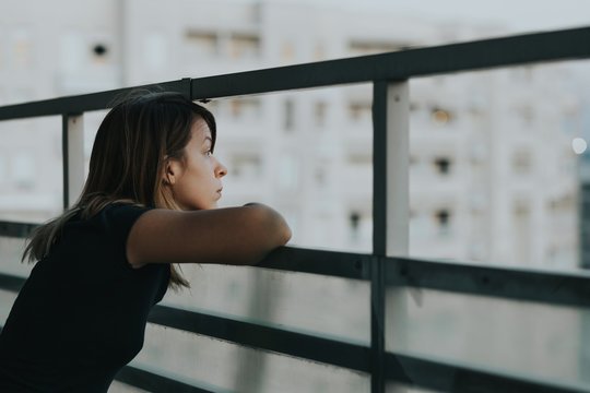 Young sad woman looking outside through balcony of an apartment building