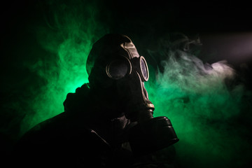 Gas mask with clouds of smoke on a dark background. Sign of radioactive contamination. Means for radiation protection. Danger of carbon monoxide poisoning.