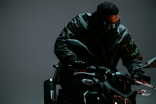 mixed race cyberpunk player in mask and futuristic glasses riding motorcycle on grey