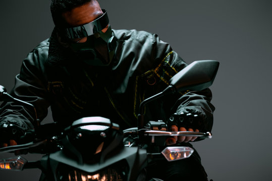 selective focus of bi-racial cyberpunk player in mask and futuristic glasses riding motorcycle on grey