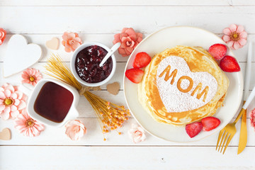 Pancakes with heart shape and MOM letters. Mothers Day breakfast concept. Above view table scene on a white wood background.