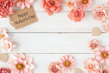Wall Mural - Happy Mothers Day frame with pink paper flowers and gift tag. Top view against a white wood background. Copy space.