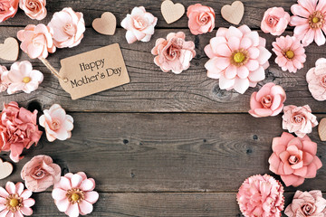 Happy Mothers Day frame with paper flowers and gift tag. Top view against a rustic wood background. Copy space.