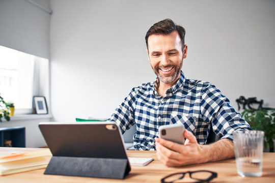 Smiling freelancer checking his smartphone while working from home office