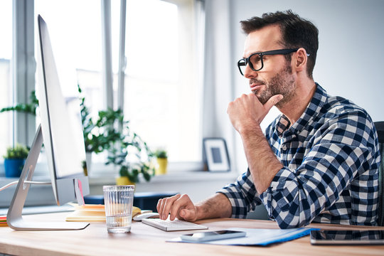 Thoughtful freelancer looking at computer while working from home office