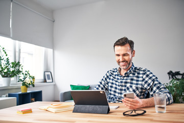 Smiling freelancer working from home sitting at a desk with digital tablet and smartphone