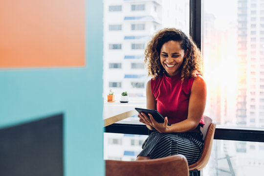 Portrait of cheerful black skin african woman smiling and using tablet for video conversation while relaxing on desk in modern office. Concept of young business people working at home.