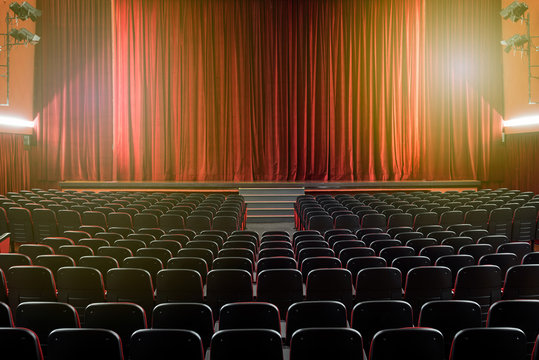 Large illuminated theatre hall with empty seats