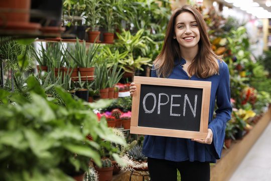 Young business owner holding OPEN sign in flower shop