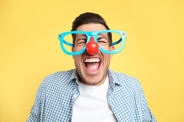 Joyful man with funny glasses on yellow background. April fool's day Fotobehang