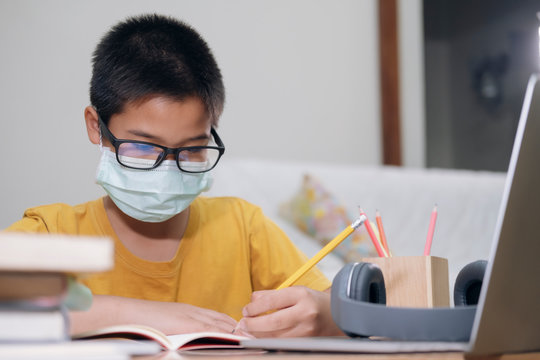 Boy wearing face masks online study at home.
