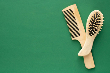 Wooden combs on a green background with place for text. Concept of healthy hair care.