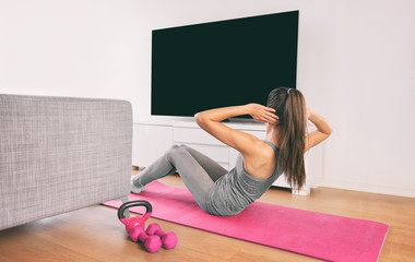 Home fitness woman doing strength training abs situps bodyweight floor exercises watching online livestream workout web videos casted on smart tv in living room of house or apartment.