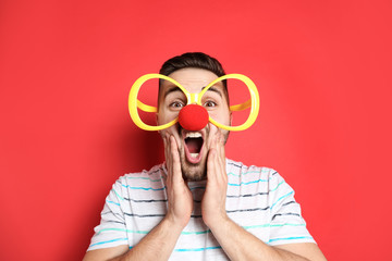 Emotional young man with party glasses and clown nose on red background. April fool's day