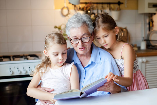 Reading book at home. Grandmother reads fairy tale. Kids listen to granny story in cozy kitchen. Happy family leisure. Children and senior woman togetherness. Lifestyle authentic moment.