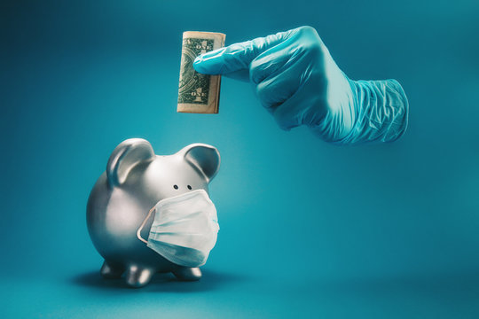 Concept of saving money during the time of infectious disease pandemic. A hand inside protective, surgical glove holding money above piggy bank with face mask.