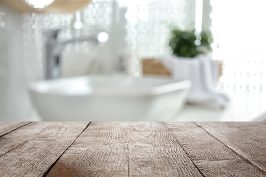 Empty wooden table and blurred view of stylish bathroom interior