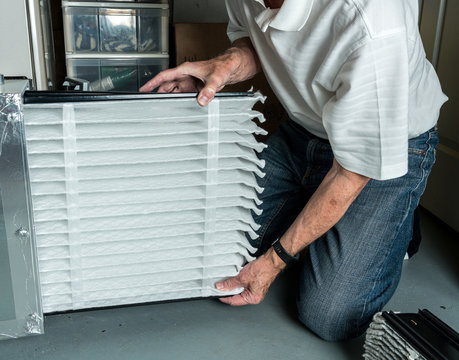 Senior caucasian man checking a clean folded air filter in the HVAC furnace system in basement of home