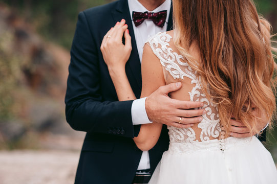 Groom in black suit and bow is holding a bride with long blonde hair