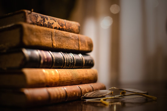 A vintage pile of five old brown leather books with eye glasses on a wood table.