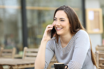 Happy woman talking on the phone in a coffee shop