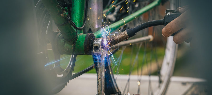 Welding an old crank or axle which was broken on an older vintage city bicycle. Man seen using a welding gun on a bicycle crank.