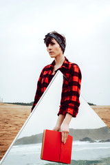 Serious pensive young female in casual red and black checkered shirt standing on sandy beach with red book in hand and large mirror with sea and rocks reflection